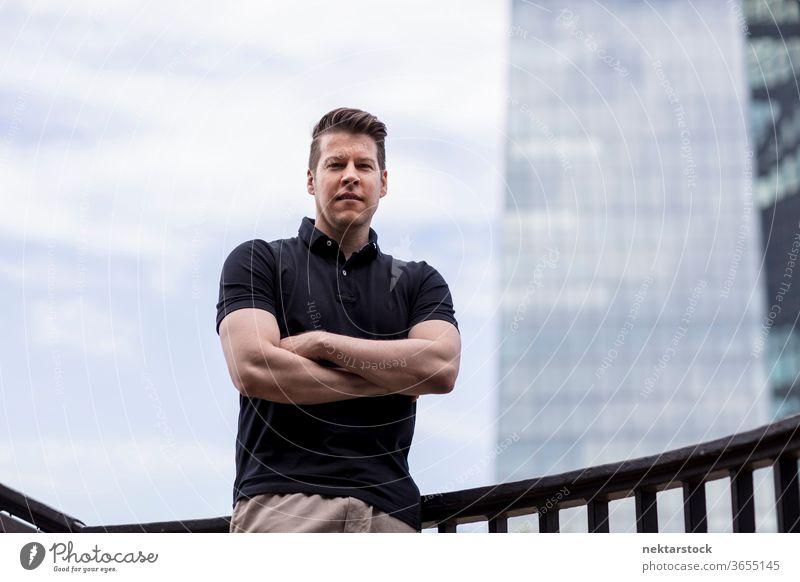 Mann mit verschränkten Armen am Himmel und Gebäudehintergrund Erwachsener Wolkenkratzer Kaukasier mittlere Aufnahme urban gutaussehend Model eine Person