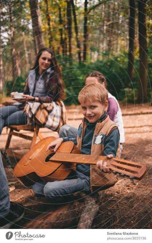 Glückliche Familie auf einem Campingausflug zur Entspannung im Herbstwald. Ein Junge hält eine Gitarre in den Händen fallen Natur Vater Mutter Zusammensein Spaß