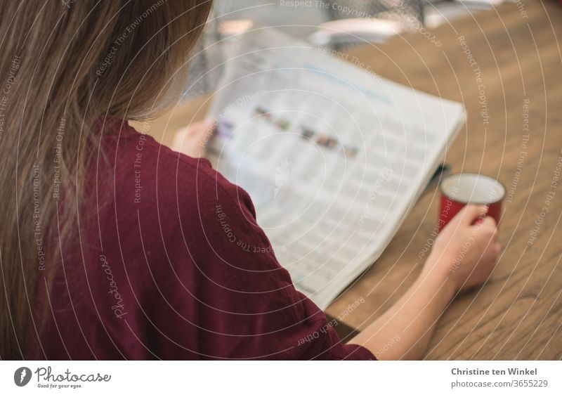 Druckerzeugnis I Eine junge Frau sitzt draußen am Tisch und liest die Zeitung. Mit der rechten Hand hält sie einen roten Kaffeebecher. Fast verdeckt von der Zeitung liegt ein Smartphone auf dem Tisch.