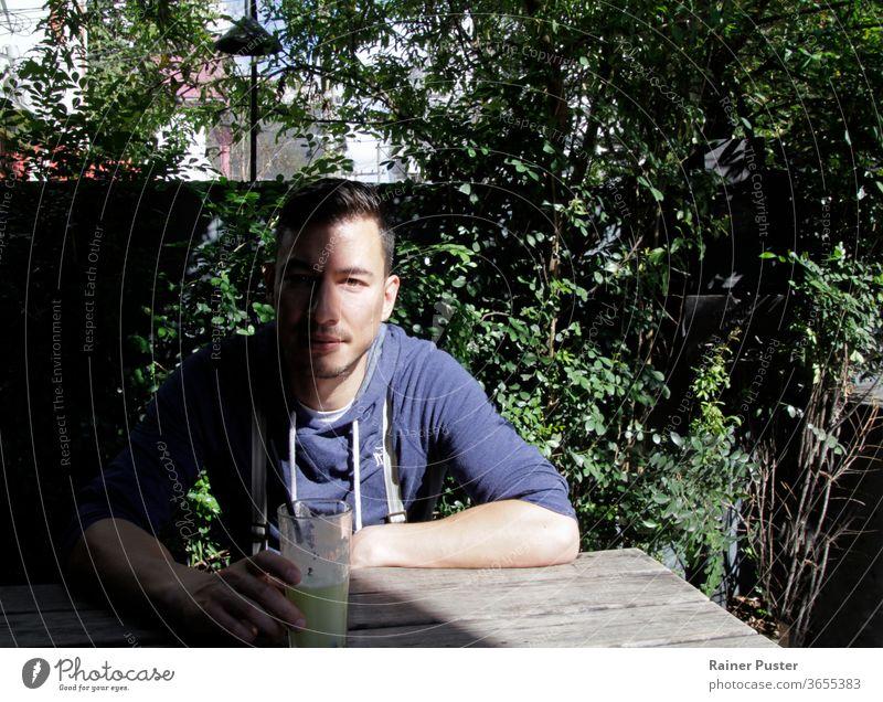 Bildnis eines gut aussehenden jungen Mannes mit einem Schatten, der sein halbes Gesicht verdeckt Erwachsener attraktiv Hintergrund lässig bedeckt eurasisch