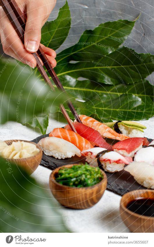 Nahaufnahme einer Hand, die ein Suchi mit Stäbchen von einem Teller nimmt Sushi unter Essstäbchen verzehrfertig Essen Sashimi Brötchen Sushi-Bar Blatt