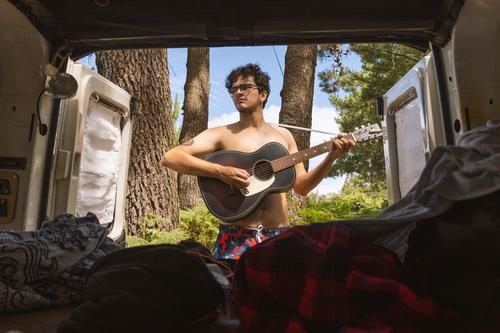 Typ, der im Wald (Camping) Abenteuergitarre spielt, vom Inneren eines Minivans aus gesehen Erholung Gitarre Tourismus Reise Lager Ausflug außerhalb jung Lächeln