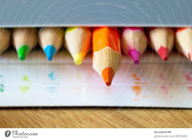 Farbstifte in einer kartongrauen Schachtel, Regenbogenfarben, orangefarbener Bleistift ragt aus Makro-, Schul- oder Büromaterial Farbe gelb rot Kunst Zeichnung