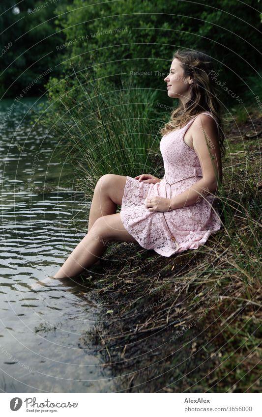 Junge Frau in rosa Sommerkleid sitzt auf einer Waldlichtung mit den Füssen im Waldsee Mädchen Gras Pflanzen Laub grün Natur Kleid barfuß barfüßig schlank