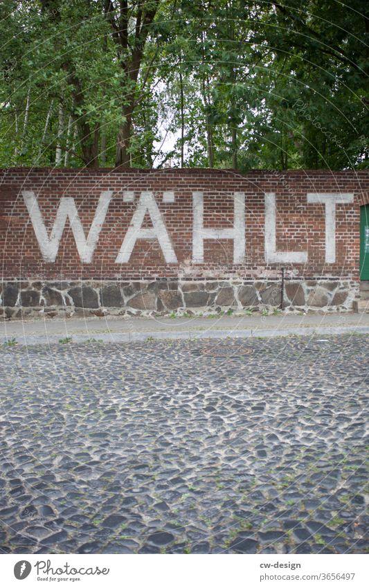 WÄHLT an eine Backsteinwand gemalt Buchstaben Schilder & Markierungen Schriftzeichen Schriftzug weiß Kommunizieren Wort Text Textfreiraum Textfreiraum oben