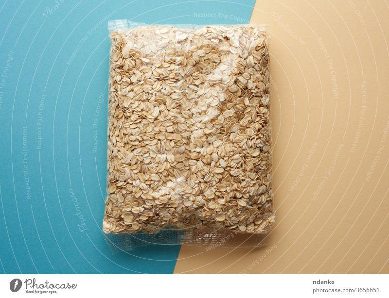 Haferflocken in transparenter Kunststoffverpackung auf blau-beigem Hintergrund organisch Haufen roh Samen Lebensmittelgeschäft Verpackung Polyethylen
