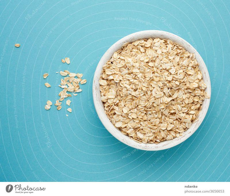 rohes Hafermehl in einer weißen Holzschüssel auf blauem Hintergrund Schalen & Schüsseln Haferflocken Diät organisch Bestandteil trocknen hölzern Lebensmittel