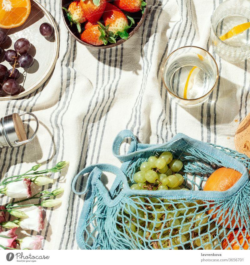Sommerpicknick Flatlay, Früchte, Beeren und Zitronenwasser auf gestreifter Baumwolldecke Picknick Lebensmittel Essen Diät frisch Brille Wasser Zitrusfrüchte