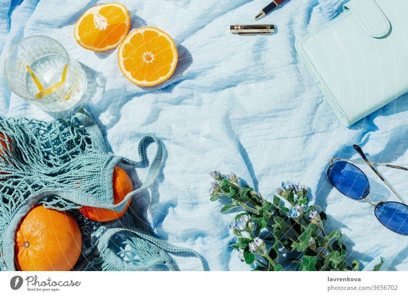 Picknick im Sommer mit Früchten, Blumen und Zitronenwasser auf einer blauen Decke Brille Wasser Zitrusfrüchte saisonbedingt frisch Einkaufsnetz
