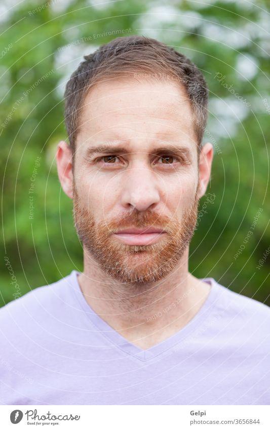 Porträt eines lässigen bärtigen Mannes in einem Park männlich jung gutaussehend Model Typ Vollbart besinnlich Denken ernst Jeansstoff attraktiv Menschen