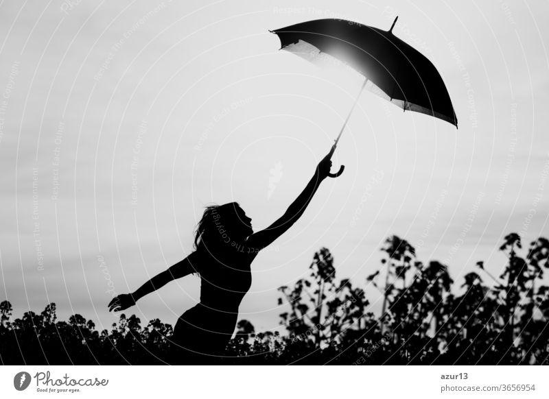 Unplugged freie Silhouette Frau Regenschirm bis zum schwarz-weißen Himmel. Naturmädchen an windigem, regnerischem Tag hat Abenteuerfernweh. Wunderbare Szene von Vorstellungskraft und Aufbruch zu neuen Horizonten in der Jugend