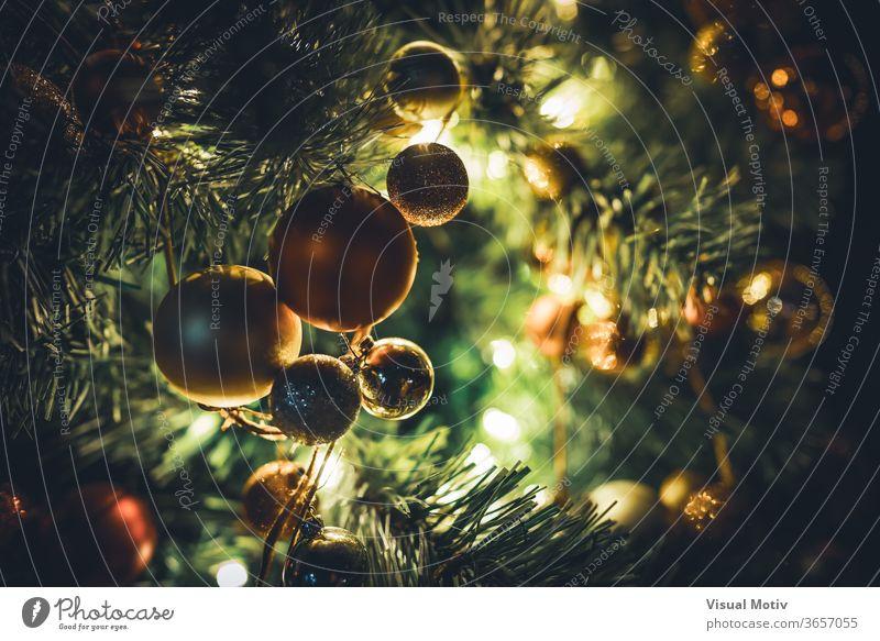 Traditionelle Weihnachtsbaumgirlande mit Kugeln, die nachts an beleuchteten Zweigen hängen traditionell Weihnachten Baum Girlande Ast Licht Feiertag feiern