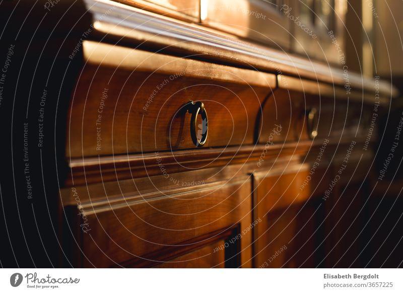 Nahaufnahme Schubladen mit Ringgriffen eines alten Buffetschrankes aus Kirschbaumholz Schrank antik möbel Einrichtung einrichten Innenaufnahme Holz