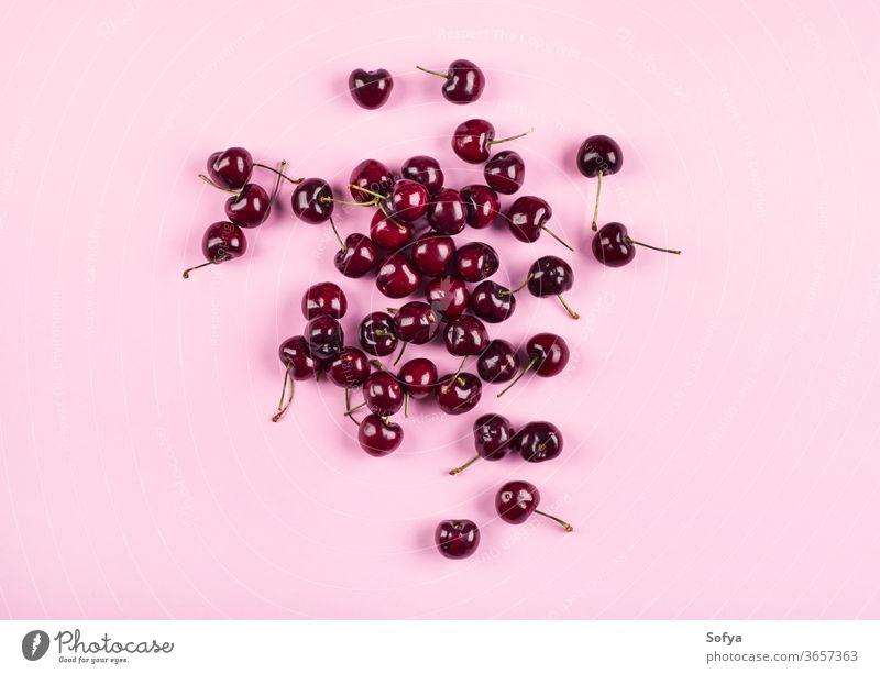Kirschhaufen auf rosa Hintergrund. Flach gelegt Kirsche produzieren Ernte Mode Design Lebensmittel Sommer Muster flache Verlegung Frucht Natur Textur Frühling