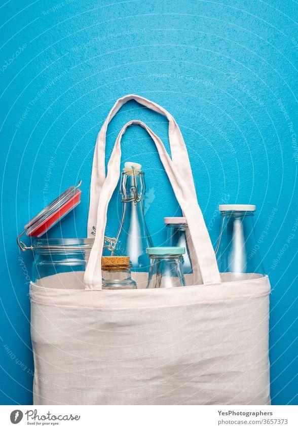 Nicht-Kunststoffbehälter für Lagerung und Einkauf. Baumwollbeutel mit Glasflaschen und -gläsern obere Ansicht Hintergrund Tasche blanko blau Großeinkauf kaufen