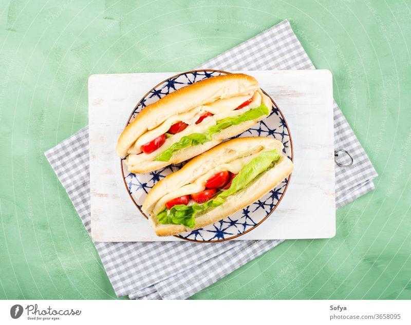 Baguette-Sandwich mit Tomaten und Käse Belegtes Brot U-Boot Mittagessen Sub hoagie flache Verlegung geschmolzen Gemüse Draufsicht Salatbeilage hölzern grün