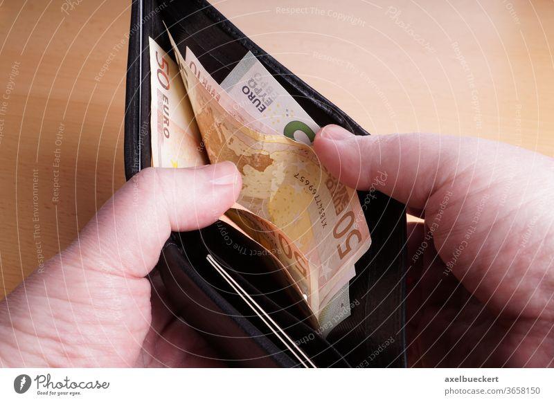 Portemonnaie mit Euro-Scheinen portmonee Geld Geldscheine Bargeld Brieftasche Finanzen Geldbörse Hand offen zeigen schwarz Leder bezahlen EUR Vermögen