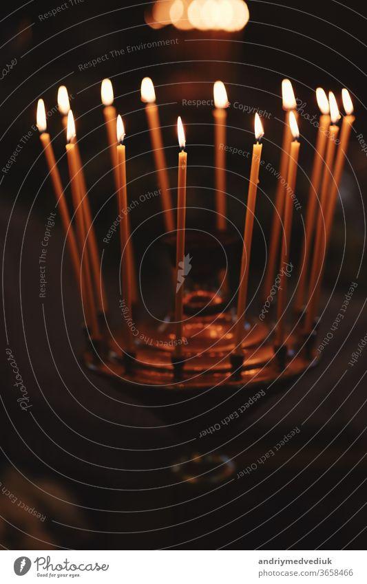 Brennende Kerzen auf Bronze-Kerzenständer vor dunklem Hintergrund zu Hause.Kerzen im Innenraum. Vintage-Stil. Ruhige romantische Atmosphäre. Horizontales Bild für Design.