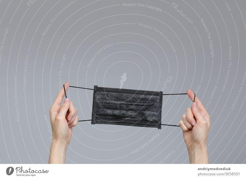 Schwarze medizinische Gesichtsschutzmaske mit Frau, die die Hand hält. medizinische Maske in den Händen. Platz für Text. selektiver Fokus Mundschutz schützend