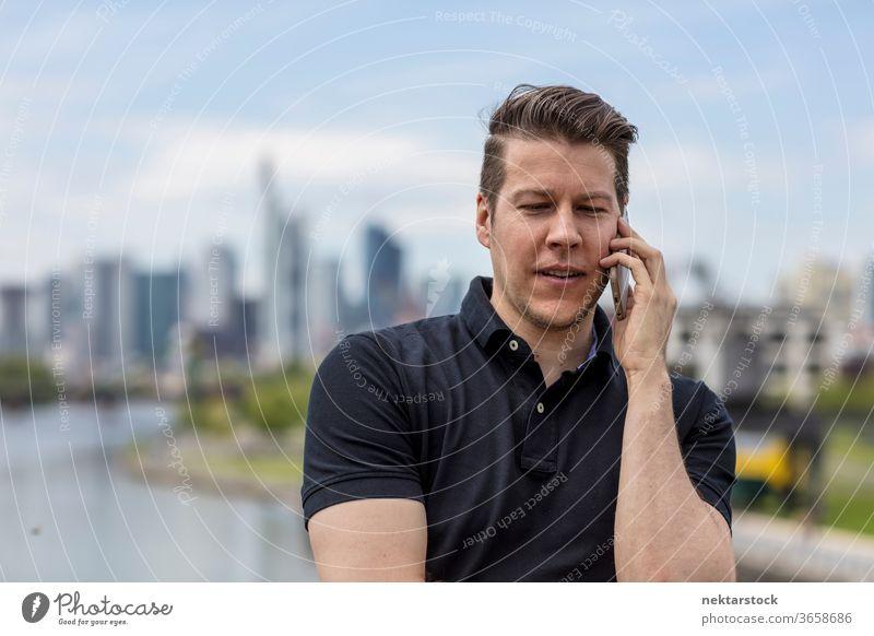 Mann im Gespräch über Mobiltelefon und Stadtsilhouette Erwachsener Skyline Handy Wolkenkratzer Metropole Mobiltechnologie Telekommunikation Hauptfluss modern