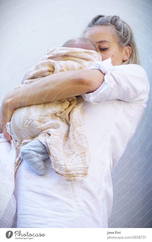 Mutter hält ihr neugeborenes Kind in den Armen. Junge Frau Liebe Baby Mutterschaft Glück halten festhalten klein Familie beige weiß hell Geborgenheit Porträt