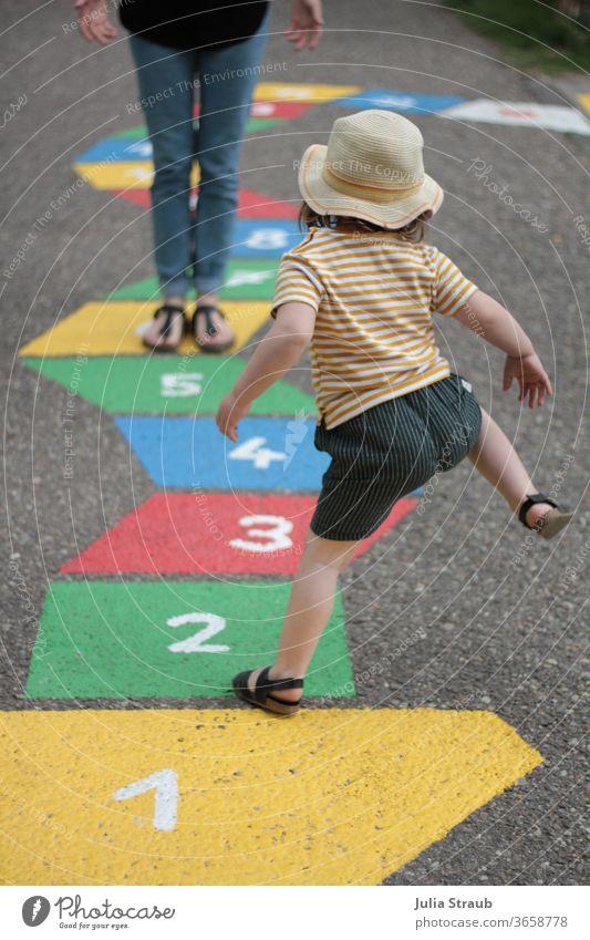 1 2 3 Kleinkind mit Hut und gestreiften T-shirt in Sandalen hüpft ein Strassenspiel Himmel & Hölle Mädchen Sommer lustig witzig springen hüpfen Erwachsene