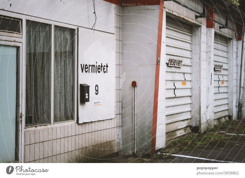 alte Garage mit Parkplätzen davor zur Vermietung grau Fassade Garagentor Gebäude Mauer Bauwerk Kacheln Fenster Tür Menschenleer Unbewohnt Rolltor runtergekommen