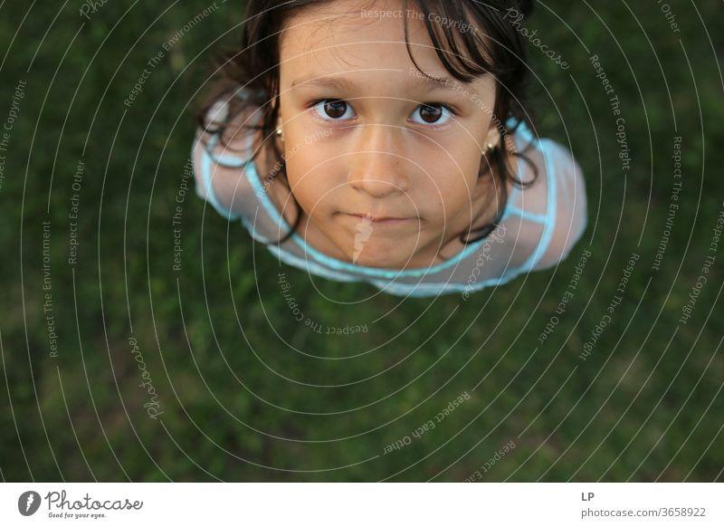 Mädchen, das in die Kamera schaut Blick in die Kamera beobachten neugierig nach unten Neugier Auge Achtsamkeit Kinderspiel Kindheitserinnerung Kinderwunsch