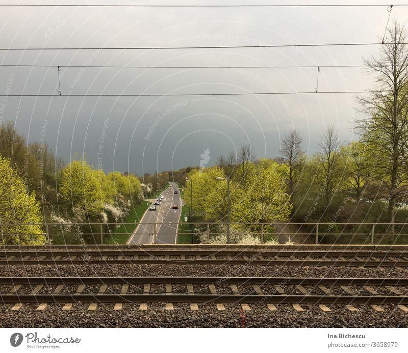 Zwischen elektrische Kabeln , die der Himmel schneiden und Zug Schienen mit einem Geländer, parallel zum den Kabeln läuft eine Straße auf dem sieben Autos in der Ferne zu sehen sind. Rechts und links in Bild stehen Bäume in helle und dunkele grüne Töne.