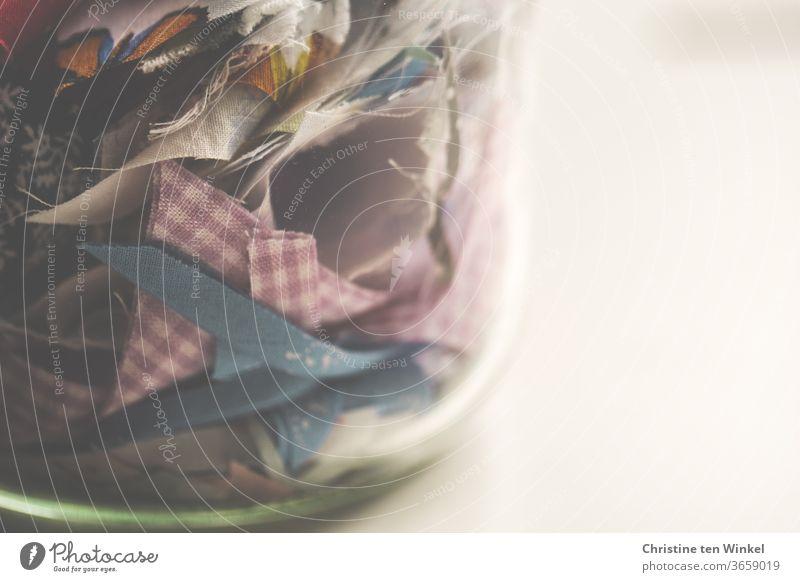 Bunte Stoffreste in einem dickwandigen Glas. Nahaufnahme mit Platz für Text Stoffschnipsel Schnipsel Reste Einmachglas aufbewahren aufheben Nähen Handarbeit