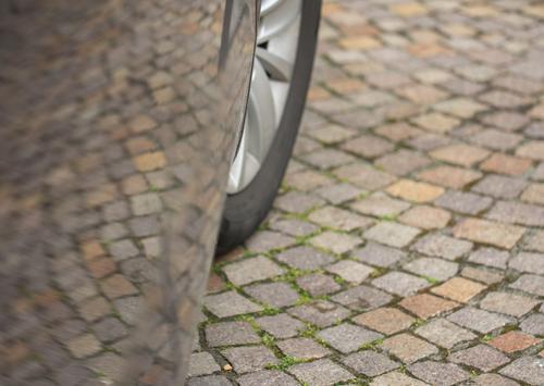 Kopfsteinpflaster mit Spiegelung im Lack einer Autotür. Zu sehen ist auch ein Teil des Vorderrades Reflexion & Spiegelung Autolack Natursteinpflaster Autoreifen