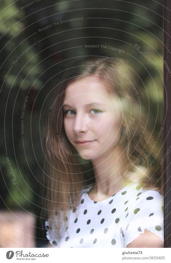 Porträt eines lächelnden Mädchens durch ein Fenster Halbprofil Zentralperspektive Schwache Tiefenschärfe Unschärfe Reflexion & Spiegelung Schatten Licht Tag