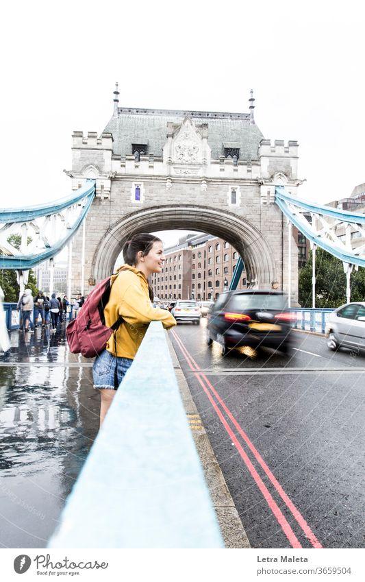 Mädchen in der Londoner Brücke in einem regnerischen Tag Junge Frau junges Mädchen Teenager Smiley Lächelndes Gesicht glückliches Mädchen gelb