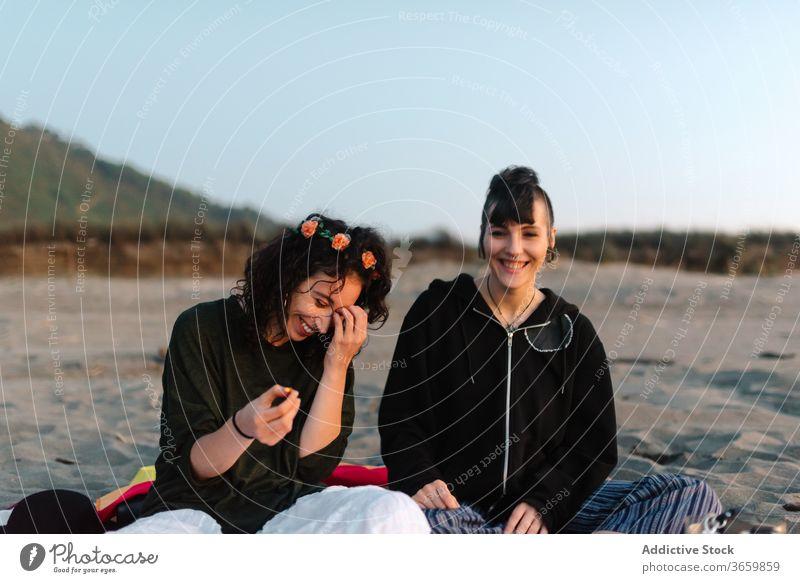 Fröhliche Freundinnen verbringen Zeit miteinander am Sandstrand bei Tageslicht sich[Akk] entspannen Strand Tourismus Paar Zusammensein Zeit verbringen Lachen