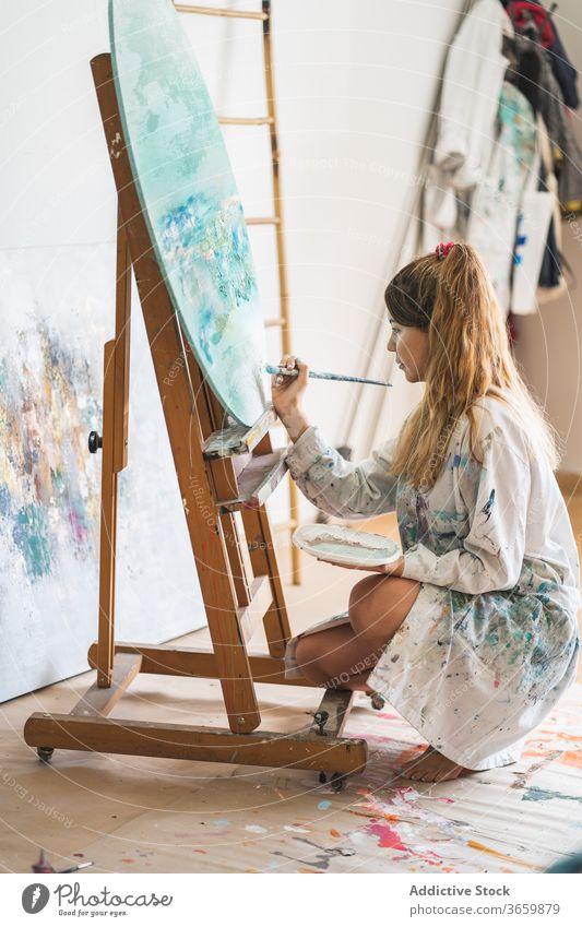 Weibliche Künstlerin malt Bild auf Staffelei Farbe Leinwand Meereslandschaft Frau kreativ Kunst Talent jung Pinselblume zeichnen Lifestyle Hobby Inspiration