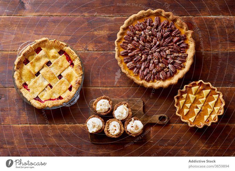 Vielfalt von Danksagungstorten auf Holztisch. Pasteten Erntedankfest Lebensmittel Pekannuss Apfel Kürbis Varieté Saison Herbst backen Abendessen saisonbedingt