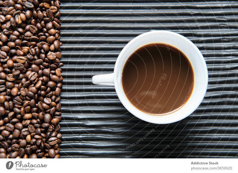 Tasse Kaffee und Kaffeekörner auf dem Tisch Bohne Tradition Kaffeemaschine Getränk trinken aromatisch Geysir frisch Koffein Aroma natürlich geschmackvoll heiß