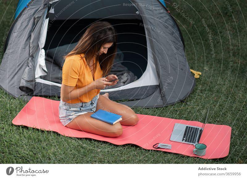Junge Frau benutzt Geräte beim Camping Lager Apparatur benutzend Smartphone modern Zelt Tourist positiv Natur jung lässig Laptop Wiese Browsen ruhen Urlaub