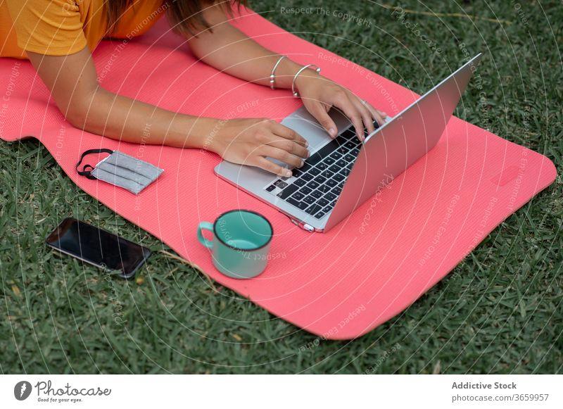 Anonyme Frau benutzt Geräte beim Camping Lager Apparatur benutzend modern Zelt Tourist positiv Natur jung lässig Laptop Wiese liegend ruhen Urlaub Handy