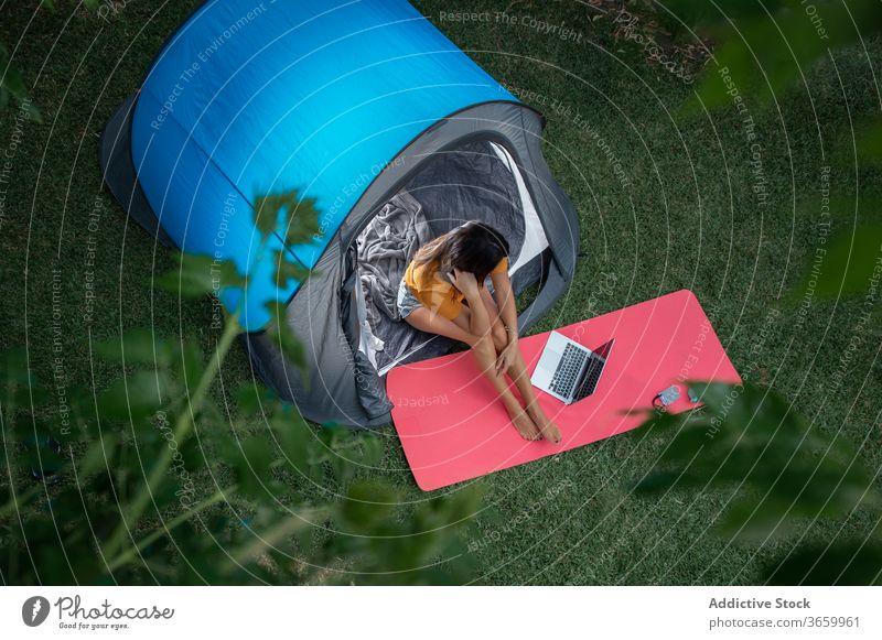 Junge Frau benutzt Geräte beim Camping Lager Apparatur benutzend modern Zelt Tourist positiv Natur jung lässig Laptop Wiese ruhen Urlaub sich[Akk] entspannen