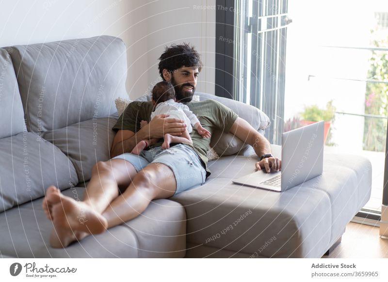 Beschäftigter Vater mit Kleinkind benutzt Laptop Baby Arbeit freiberuflich Sofa beschäftigt neugeboren Projekt benutzend männlich Vaterschaft Netbook heimwärts