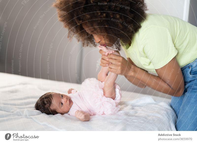 Zufriedene ethnische Mutter spielt mit Baby Säugling spielen Frau Angebot neugeboren bezaubernd Inhalt Spaß haben heimwärts Afroamerikaner schwarz heiter Eltern