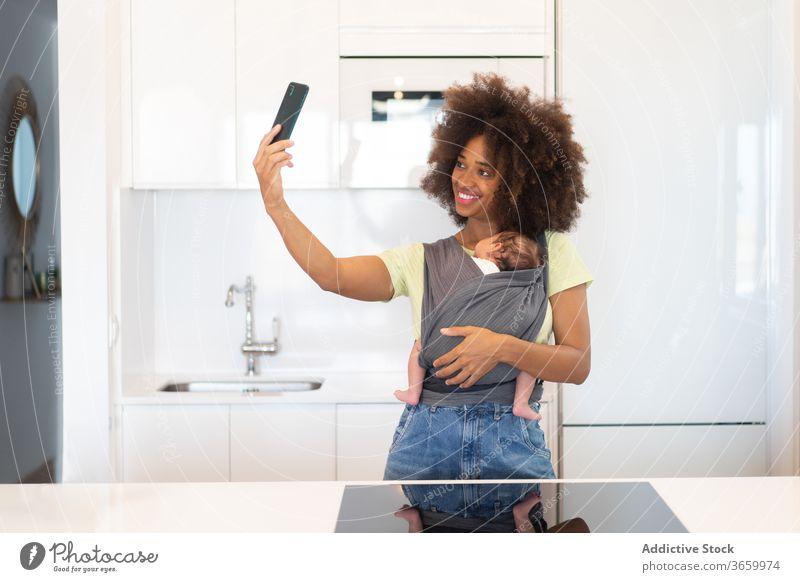Afroamerikanische Mutter, die Selbsthilfe mit ihrem Baby nimmt schlafen Babytragetuch Selfie Liebe Smartphone heimwärts führen benutzend Frau ethnisch schwarz