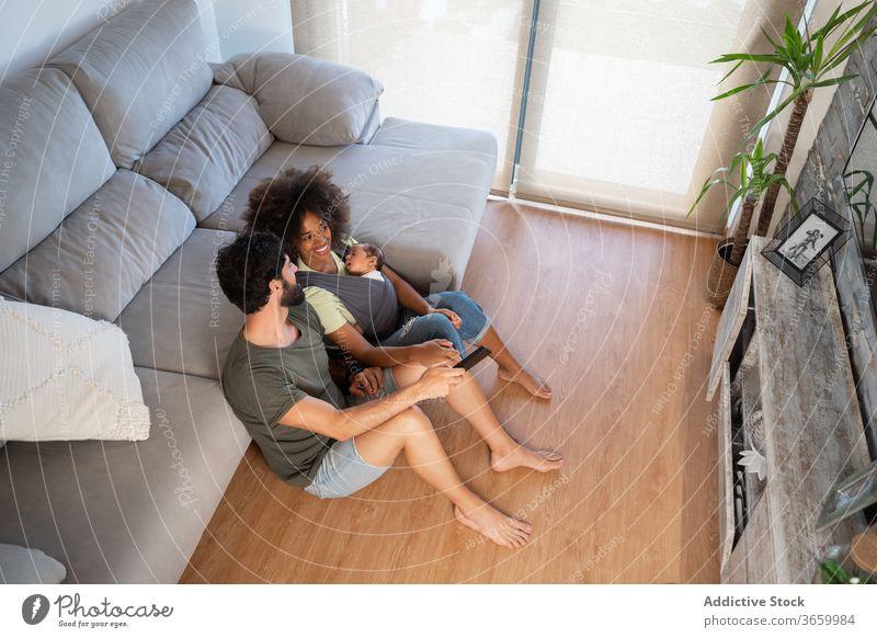 Glückliche multiethnische Familie entspannt zu Hause Pflege positiv neugeboren Freude heiter rassenübergreifend Mutter gemütlich Baby Vater Bonden schwarz