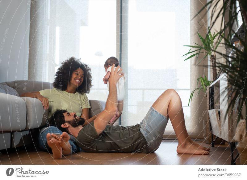 Glückliche multiethnische Familie entspannt zu Hause Einheit sich[Akk] entspannen heimwärts Zusammensein spielen Baby neugeboren bezaubernd Inhalt Spaß haben