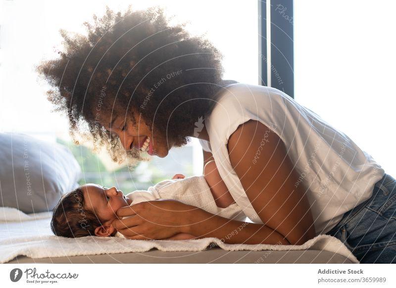 Zärtliche ethnische Frau streichelt Baby Mutter niedlich Mutterschaft heimwärts spielen Angebot Sofa Streicheln neugeboren Zusammensein multiethnisch