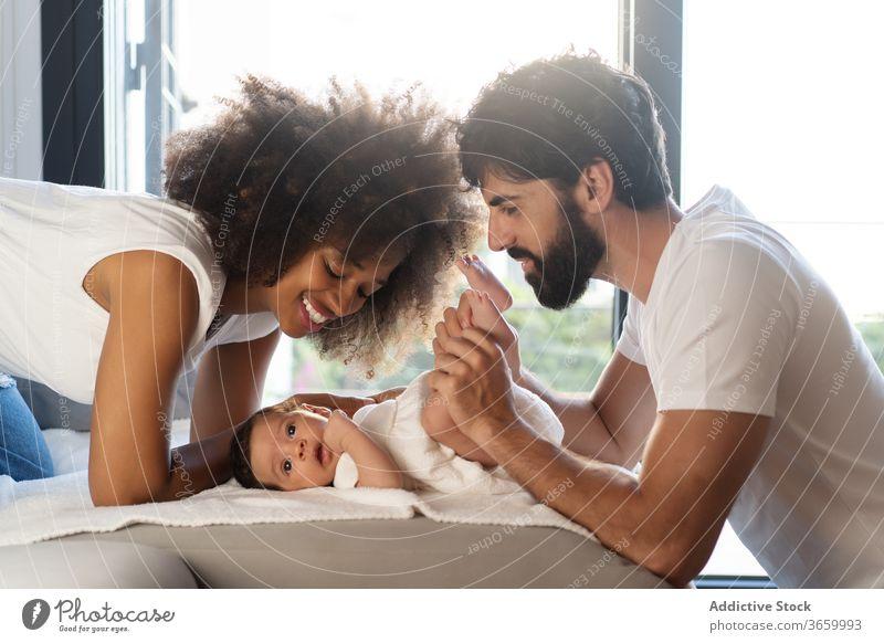 Zärtliches Streicheln eines Babys aus mehreren Rassen niedlich Familie heimwärts spielen Angebot Sofa neugeboren Zusammensein Eltern multiethnisch