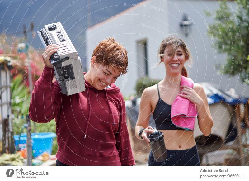Aufgeregte Sportlerinnen mit Ghettoblaster im Hinterhof ruhen Boombox Land Glück aufgeregt zuhören Fitness Sportbekleidung sich[Akk] entspannen Training