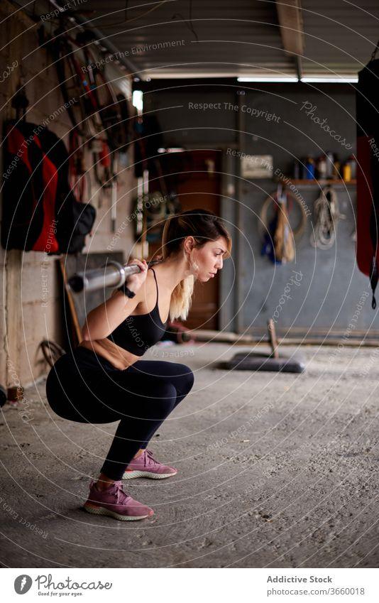 Schlanke Sportlerin beim Training mit Langhantel im Fitnessstudio Curl-Hantel Übung Konzentration passen Gerät sportlich Fokus Körper Sportkleidung stark