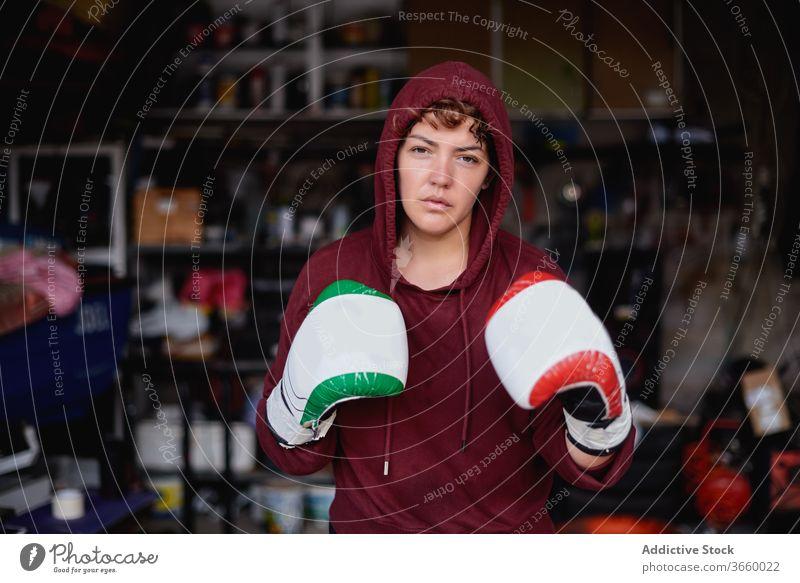 Entschlossene Sportlerin beim Schattenboxen im Fitnessstudio Boxer Boxsport Handschuh Bowle ernst Bestimmen Sie Training Garage stark Konzentration passen